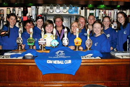 The netball teambehind The Jolly Huntsman's bar with Helen Curtis and their new hoodies